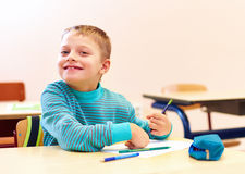 Cute boy with special needs writing letters while sitting at the desk in class room Stock Photo