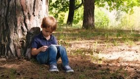 Cute boy spends time playing in the tablet, sitting by a tree in the Park or forest. Technologies and generation Z. stock footage