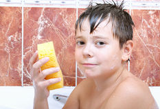 Cute boy with sponge in bathtub Royalty Free Stock Images
