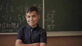 Cute boy stand in the classroom background of blackboard. Education. Elementary school.  stock video footage