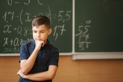 Cute boy stand in the classroom background of blackboard. Education. Elementary school.  stock photo