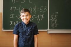 Cute boy stand in the classroom background of blackboard. Education. Elementary school.  royalty free stock image