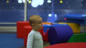 A cute boy standing in the children's play area at the airport in slow motion. Little cute boy standing in the children's play area among the big colorful stock footage