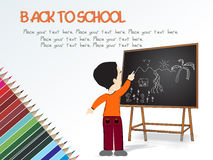 Cute boy standing in front of blackboard Stock Image