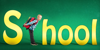 Cute boy standing instead of a letter C in the word School Stock Photos