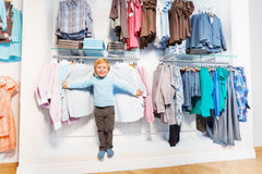 Cute boy stands among clothes on hangers and shelf Stock Photo