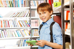 Cute boy stands and holds books in library Royalty Free Stock Images