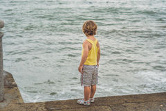 Cute boy stands on the shore watching the ocean waves Stock Image