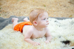 Cute boy staring. Cute baby boy staring forward while lying on a blanket outdoors Royalty Free Stock Image