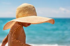 Cute boy in a straw hat on the beach royalty free stock photo
