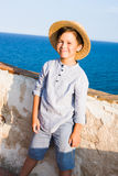 Cute boy in straw hat smiles against sea Stock Image