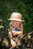 Cute boy with straw hat trying climb on a tree Stock Image