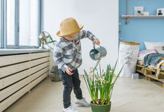 Cute boy in straw hat with a watering can. Watering plant Royalty Free Stock Photos