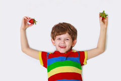 Cute boy with strawberry in hand,. Shows a healthy white smile, lying on a light background Royalty Free Stock Images