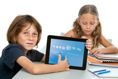 Cute boy student doing maths on digital tablet. Close up portrait of boy student doing maths on digital tablet at desk Royalty Free Stock Images