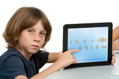 Cute boy student pointing on tablet. Royalty Free Stock Photo