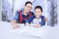 Cute boy studying with father at home Royalty Free Stock Photos