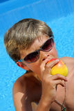 Cute Boy with sun glasses eating a delicious apple. A 10 year old cute American - German boy with sun glasses sitting at a swimming pool and enjoying eating a Stock Photography