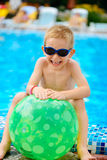 Cute boy in sunglasses sitting at pool Royalty Free Stock Photo