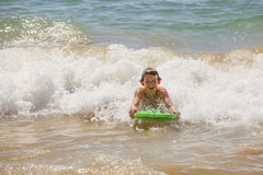 Cute boy surfing in the waves. Cute boy has fun surfing in the waves royalty free stock photos