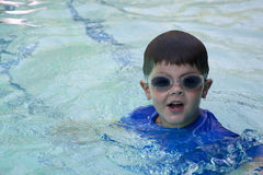 Cute boy with swimming goggles. Cute boy swimming in pool wearing blue shirt and goggles Stock Images