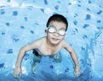 Cute boy swimming and playing in swimming pool.  Stock Images