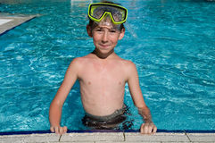 Cute boy in a swimming pool. Portrait of cute boy wearing in yellow goggles in a swimming pool Royalty Free Stock Images