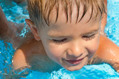 Cute boy swimming in the pool Stock Images