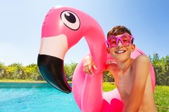 Cute boy with swimming ring relaxing by the pool. Portrait of teenage boy wearing star shaped sunglasses, holding flamingo inflatable ring and relaxing by the royalty free stock images