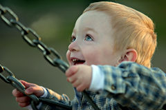 Cute boy on swing. Cute young redheaded boy on a swing, pure joy. shallow depth of field with focus on his left eye royalty free stock photo