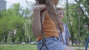 Cute boy swinging on a swing beautiful girl with long hair, smiling. A couple of happy children. Funny carefree kids in stock footage