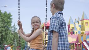 Cute boy swinging on a swing beautiful girl with long hair, smiling. A couple of happy children outdoors. Funny carefree stock video footage