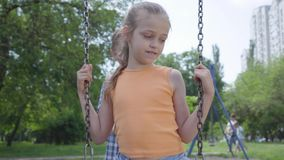 Cute boy swinging on a swing beautiful girl with long hair, smiling. Small couple of happy children. Funny carefree kids stock footage