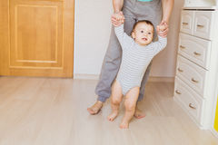 Cute boy taking first steps holding mother`s hands. Stock Images