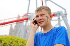 Cute boy talking a cell phone at amusement park Royalty Free Stock Photo