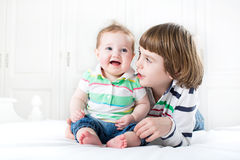 Cute boy talking to his baby sister Stock Photo