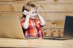 Cute boy talks on phones Stock Photo