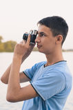 Cute boy teenager with vintage rangefinder camera. Royalty Free Stock Photography