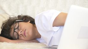 Cute boy teenager wearing glasses sleeps on couch next to laptop. 4k stock footage