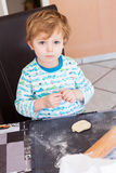 Cute boy of three years helping to bake in home kitchen, Stock Photos