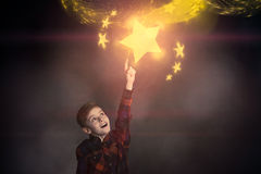 Cute Boy Touching a Glowing Yellow Star Over Him Stock Image