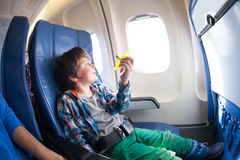 Cute boy with toy plane sit by the airplane window Stock Photo