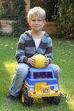 Cute boy on a toy truck Stock Photography
