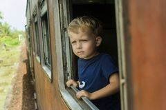Cute boy in train. Cute boy is looking through the window in the Sri Lanka train with a skepticism and melancholy on his face royalty free stock image