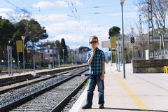 Cute boy at the train station waiting for the train. Stylish cute boy at the train station waiting for the train in summer Royalty Free Stock Images