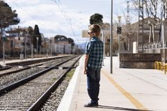 Cute boy at the train station waiting for the train. Stylish cute boy at the train station waiting for the train in summer Royalty Free Stock Image