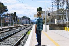 Cute boy at the train station waiting for the train. Stylish cute boy at the train station waiting for the train in summer Stock Images