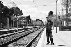 Cute boy at the train station waiting for the train. Stylish cute boy at the train station waiting for the train in summer Stock Photo