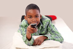 Cute boy with TV remote Stock Images