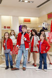 Cute boy with two little girls trying on clothes together. With mannequins in the store childrens clothes stock photo